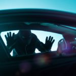 Car Robber Concept Photo. Robber Looking Thru Car Window. Carjacking Theme.